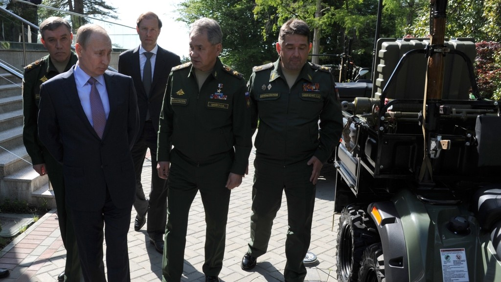 2844847 05/12/2016 From left, foreground: President Vladimir Putin and Defense Minister Sergei Shoigu observing military technology, following the meeting with military commanders and industrial executives of the military-industrial complex at his Bocharov Ruchei residence in Sochi, May 12, 2016. From left, background: General Valery Gerasimov, Chief of Staff, Deputy Defense Minister, and Industry/Trade Minister Denis Manturov. Michael Klimentyev/Sputnik