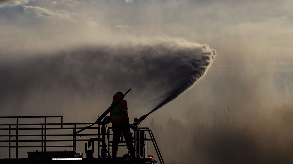 FORT MCMURRAY, CANADA - MAY 11 : Fire support crew extinguish a wildfire that erupted outside Fort McMurray, Alberta, Canada on May 11, 2016. Wildfire erupted on 3 May consuming 200 thousand hectares and destroying 90% of houses in Fort McMurray city. Amru Salahuddien / Anadolu Agency