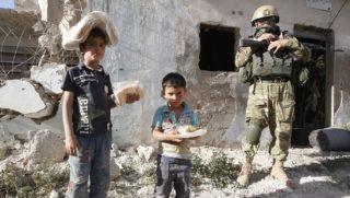 Kaukab, 2016. május 5. Szíriai gyerekek humanitárius szervezet által adományozott és az országban állomásozó orosz haderõ által kiosztott élelmiszersegéllyel egy orosz katona társaságában a szíriai Hama tartománybeli Kaukab faluban 2016. május 4-én. Az észak-szíriai Aleppóban tûzszünet lépett hatályba a damaszkuszi kormány és a felkelõk fegyveresei között az Egyesült Államok és Oroszország közbenjárására.(MTI/EPA/Szergej Csirikov)