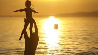 Fonyód, 2015. augusztus 28.  Fürdõzõ férfi dobja fel kislányát a Balatonban naplementekor Fonyódnál 2015. augusztus 28-án. Másodfokú hõségriasztást ad ki augusztus 29-én 0 órától szeptember 1-jén éjfélig az országos tisztifõorvos, idén ötödik alkalommal. MTI Fotó: Varga György