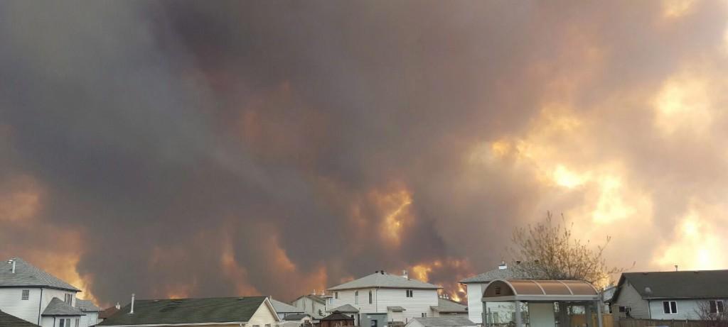 Fort McMurray, 2016. május 4. Erdõtûz füstje borítja be az eget a délnyugat-kanadai Alberta tartománybeli Fort McMurray határában 2016. május 3-án, miután a szárazság és a közel 30 fokos hõmérséklet miatt lángra kapott a növényzet. A szél miatt gyorsan terjedõ tûz fenyegetést jelent a 80 ezres város déli részének lakosságára, akik számára ideiglenes menedékhelyeket biztosítanak a hatóságok. (MTI/AP/The Canadian Press/Mary Anne Sexsmith-Segato)
