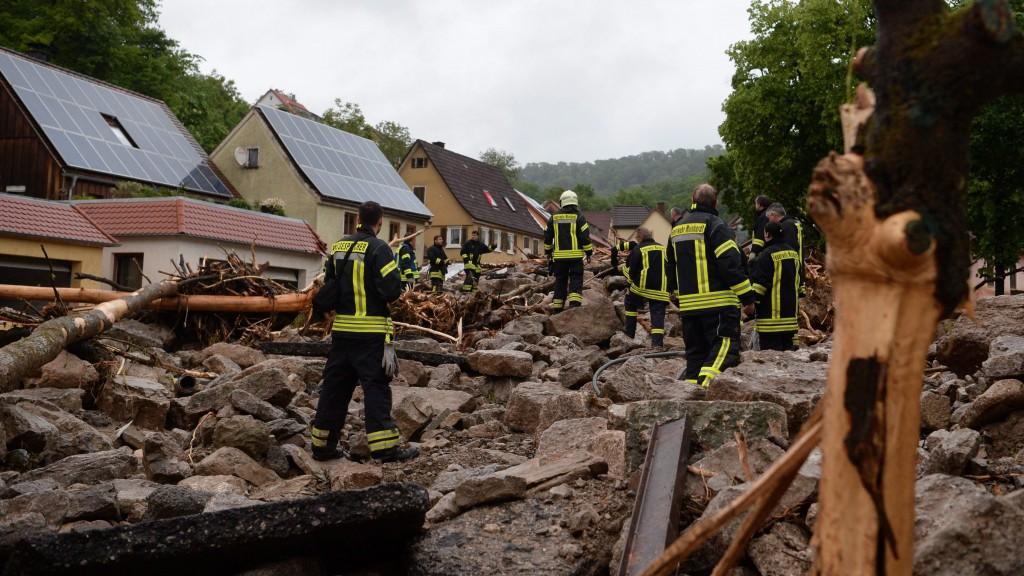 Braunsbach, 2016. május 30. Tûzoltók egy áradásból visszamaradt hordalékhalmon a dél-németországi Braunsbachban 2016. május 30-án, miután elõzõ éjjel hatalmas mennyiségû csapadék zúdult le Baden-Württembergben és több déli tartományban. A súlyos viharok és áradások miatt eddig legkevesebb hárman életüket vesztették és többen megsérültek. (MTI/EPA/Franziska Kraufmann)