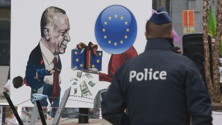 """A picture taken on March 18, 2016 shows a police officer walking past a placard depicting German Chancellor Angela Merkel (R) giving money to Turkish President Recep Tayyip Erdogan and reading """"not to be accomplices to crime, involves supporting peace, democracy and human rights"""" as Kurdish people take part in a protest to call for an end of the Turkish State terror in Kurdistan, during the European Union summit in Brussels.Underscoring tension with Brussels, Turkish President Recep Tayyip Erdogan accused the Europeans of supporting the outlawed Kurdistan Workers' Party (PKK) days after a bombing in Ankara claimed by Kurdish rebels that killed 35 people. Many European Union states have expressed concerns about Ankara's human rights record, including its treatment of the Kurds and a crackdown on critics of the government. The United Nations and rights groups fear the deal could violate international law that forbids the mass deportation of refugees. / AFP PHOTO / JOHN THYS"""