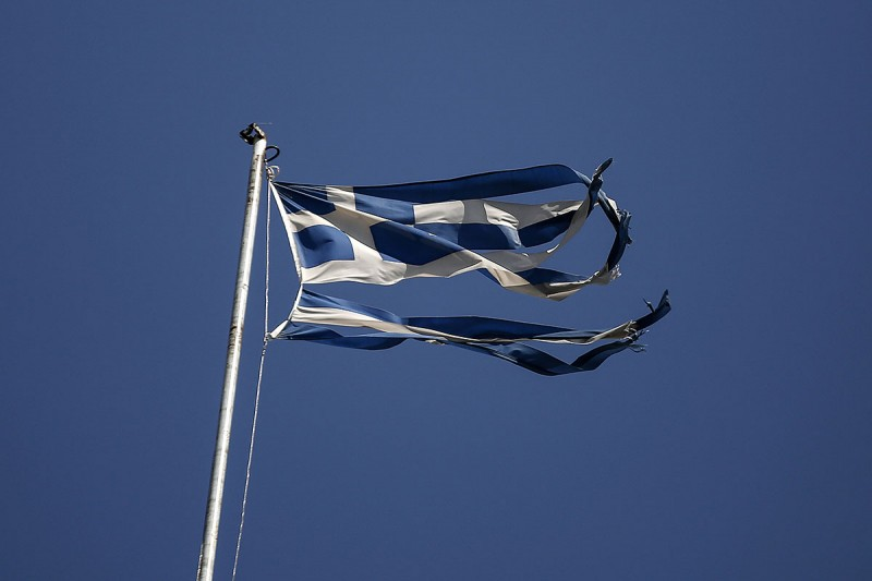 A torn Greek national flag flies from the roof of a building in Athens, Greece, on Tuesday, July 21, 2015. Greece's sweeping tax changes, passed as part of a deal with creditors to receive additional bailout funds, increase the value-added tax rate from 13 percent to 23 percent. Photographer: Yorgos Karahalis/Bloomberg via Getty Images