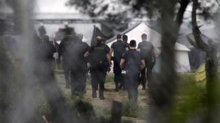 Idomeni, 2016. május 24. Görög rohamrendõrök megkezdik a macedón határ mellett fekvõ Idomeni görög falunál lévõ migránstábor kiürítését 2016. május 24-én. A táborban a becslések szerint nyolcezer-négyszáz menedékkérõ tartózkodhat. A felvétel a határ macedón oldala felõl készült. (MTI/AP/Boris Grdanoski)