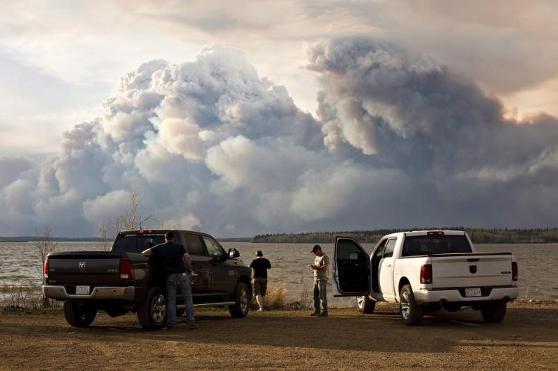 Fort McMurray, 2016. május 5. Erdõtûz füstje borítja be az eget a délnyugat-kanadai Alberta tartománybeli Fort McMurray határában 2016. május 4-én. Albertában szükségállapotot hirdettek a pusztító erdõtüzek miatt, Fort McMurraybõl 88 ezer ember menekült el, a városban 1600 épület vált lángok martalékává. (MTI/AP/The Canadian Press/Jason Franson)