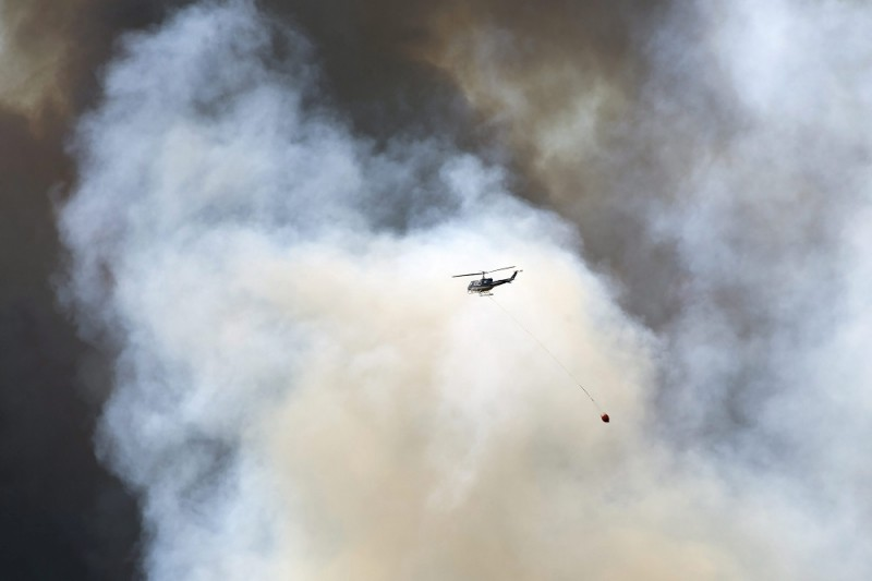 Fort McMurray, 2016. május 5. Az albertai tartományi kormány által közreadott képen tûzoltó-helikopter és erdõtûz füstje Fort McMurray fölött 2016. május 4-én, amikor erdõtüzek pusztítanak a nyugat-kanadai Alberta tartományban. (MTI/EPA/Albertai tartományi kormány/Chris Schwarz)