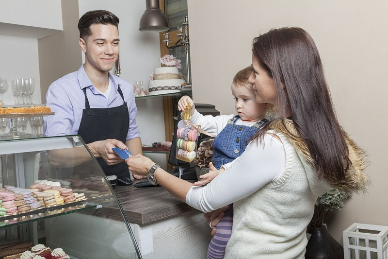 Mother and toddler standing at the cash desk of a cake shop paying for a sachet of french macaroons
