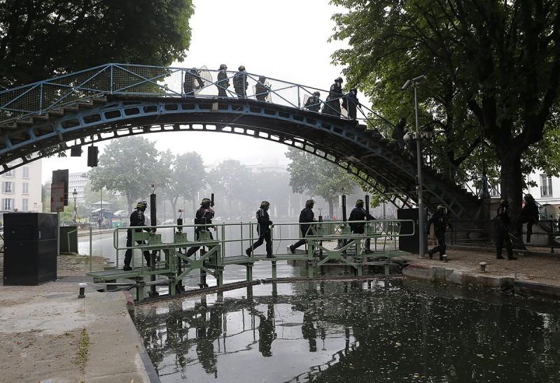Párizs, 2016. május 18.Rohamrendőrök rendbontó ellentüntetőket üldöznek egy párizsi élővíz csatornánál a francia rendőrök tüntetésén 2016. május 18-án, miután az ellentüntetők rátámadtak az utcára vonult rendőrökre. A rendőrség a megmozdulással a rendszerint erőszakos cselekményekbe torkolló, mindennapossá vált francia munkajogi reform elleni lakossági tüntetéseket kívánja elítélni. (MTI/AP/Francois Mori)