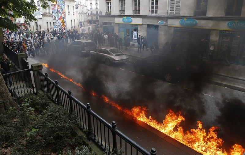 Párizs, 2016. május 18.Üzemanyag lángol az út mentén a francia rendőrök tüntetésén Párizsban 2016. május 18-án, miután ellentüntetők rátámadtak az utcára vonult rendőrökre. A rendőrség a megmozdulással a rendszerint erőszakos cselekményekbe torkolló, mindennapossá vált francia munkajogi reform elleni lakossági tüntetéseket kívánja elítélni. (MTI/AP/Francois Mori)