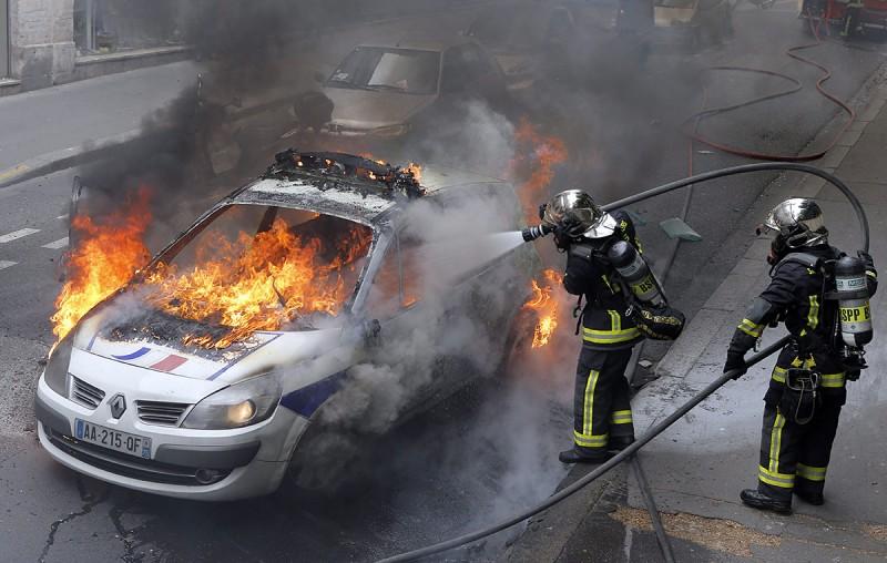 Párizs, 2016. május 18.Tűzoltók egy lángoló rendőrautónál a francia rendőrök tüntetésén Párizsban 2016. május 18-án, miután ellentüntetők rátámadtak az utcára vonult rendőrökre. A rendőrség a megmozdulással a rendszerint erőszakos cselekményekbe torkolló, mindennapossá vált francia munkajogi reform elleni lakossági tüntetéseket kívánja elítélni. (MTI/AP/Francois Mori)