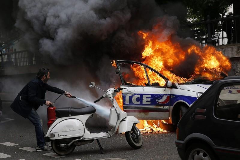 Párizs, 2016. május 18.Lángoló francia rendőrautót olt egy férfi, miután rendbontók tüntető francia rendőrökre támadtak Párizsban 2016. május 18-án. A rendőrség a megmozdulással a rendszerint erőszakos cselekményekbe torkolló, mindennapossá vált francia munkajogi reform elleni lakossági tüntetéseket kívánja elítélni. (MTI/EPA/Yoan Valat)