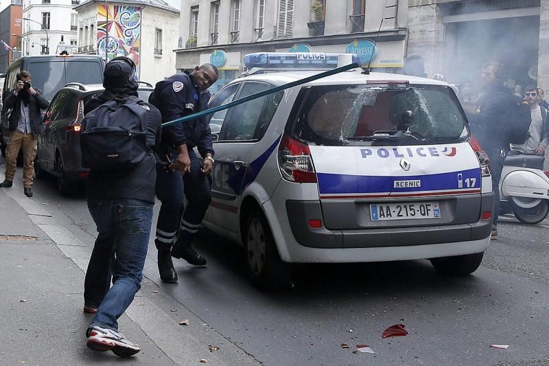 Párizs, 2016. május 18.Egy járőrautót rongáló férfi egy közbelépő rendőrre támad a francia rendőrök tüntetésén Párizsban 2016. május 18-án. A rendőrség a megmozdulással a rendszerint erőszakos cselekményekbe torkolló, mindennapossá vált francia munkajogi reform elleni lakossági tüntetéseket kívánja elítélni. (MTI/EPA/Yoan Valat)