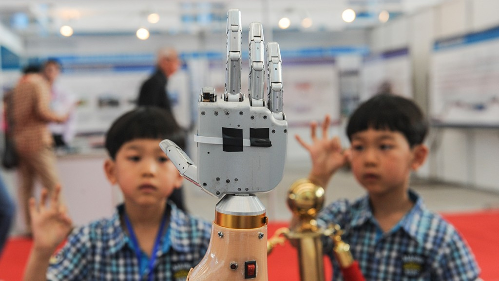 (160522) -- HARBIN, May 22, 2016 (Xinhua) -- Children look at a robot hand at the 16th Harbin International Equipment Manufacturing Exposition held in Harbin, capital of northeast China's Heilongjiang Province, May 22, 2016. (Xinhua/Wang Song) (wyl)