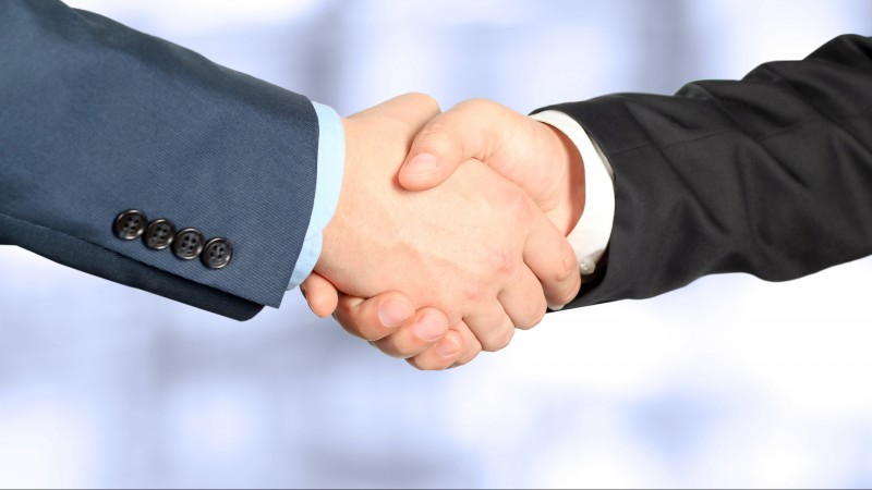The firm handshake  between two colleagues in office.