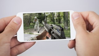 Man Playing Action Game On Smartphone
