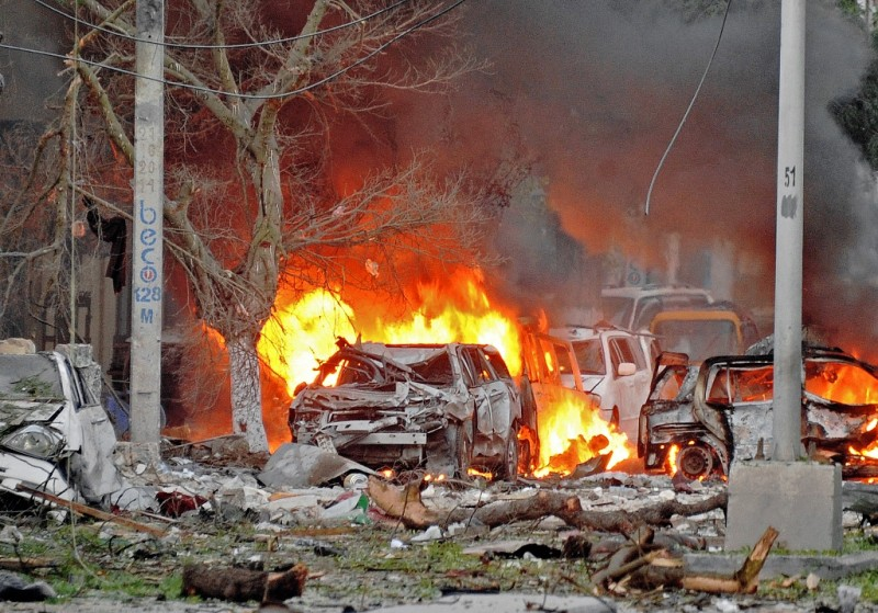 Wrecked cars burn at the scene of a terror attack at the Ambassador Hotel, after a car bomb exploded on June 1, 2016 at a top Mogadishu hotel that houses several MPs, killing several people, and followed by a gun battle. Somalia's Al-Qaeda-linked al-Shabaab group was chased out of the capital Mogadishu in 2011 but remains a dangerous threat in both Somalia and neighbouring Kenya, where it carries out frequent attacks. / AFP PHOTO / MOHAMED ABDIWAHAB