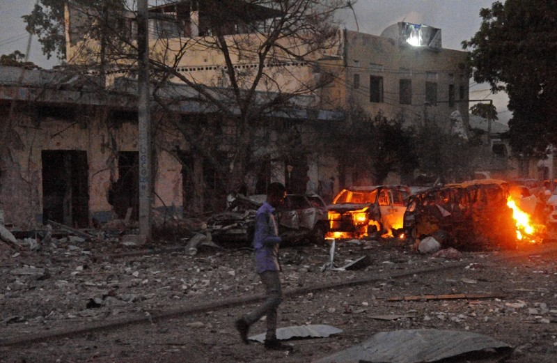 A man walks past the scene of a terror attack at the Ambassador Hotel, after a car bomb exploded on June 1, 2016 at a top Mogadishu hotel that houses several MPs, killing several people, and followed by a gun battle. Somalia's Al-Qaeda-linked al-Shabaab group was chased out of the capital Mogadishu in 2011 but remains a dangerous threat in both Somalia and neighbouring Kenya, where it carries out frequent attacks. / AFP PHOTO / MOHAMED ABDIWAHAB
