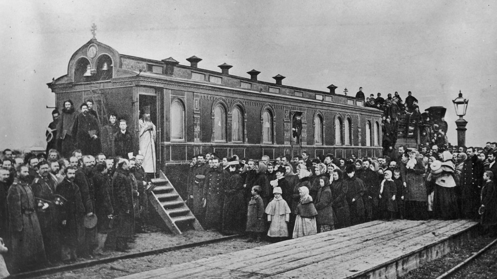 1906:  A crowd gathered to watch a Russian Orthodox service in progress in an ornate railway carriage on the Manchurian Railway.  (Photo by Topical Press Agency/Getty Images)