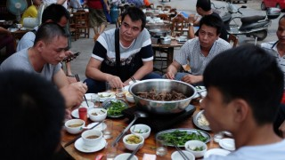 This photo taken on May 9, 2016 shows people eating dog meat at a restaurant in Yulin, in China's southern Guangxi region. International groups and celebrities, backed by millions of foreign petitioners, have rallied against an annual dog meat festival in the Chinese city of Yulin: but the protests may have backfired, residents say, spurring more people to eat man's best friend. / AFP PHOTO / GREG BAKER / TO GO WITH AFP STORY CHINA-ANIMAL-DOG-FOOD, FOCUS BY BENJAMIN CARLSON