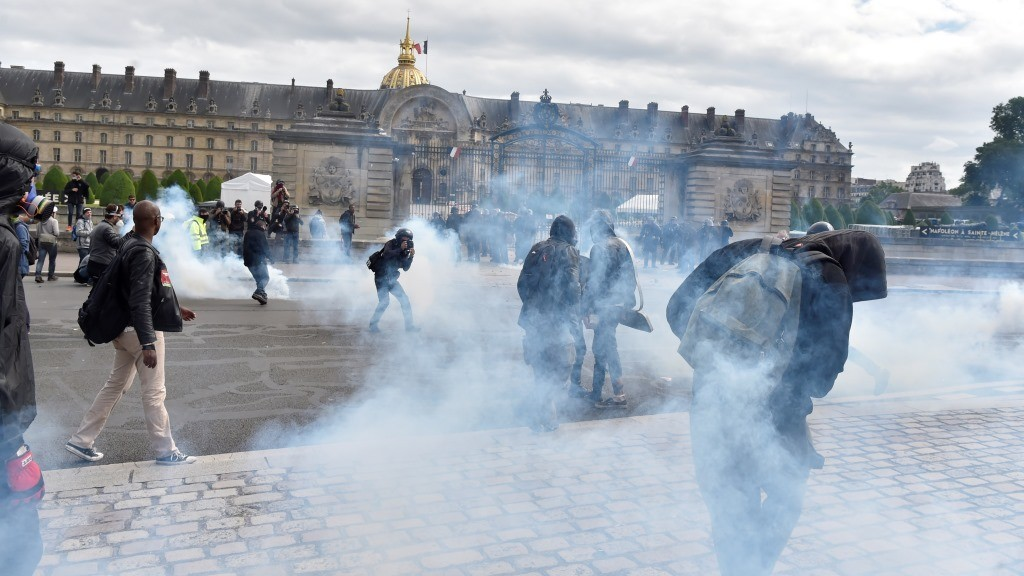 Demonstrators stand in tear gas near the Invalides during a protest against proposed labour reforms in Paris on June 14, 2016.  Strikes closed the Eiffel Tower and disrupted transport in France on June 14 as tens of thousands prepared to march against labour reforms with the Euro 2016 football championship in full swing.  / AFP PHOTO / ALAIN JOCARD