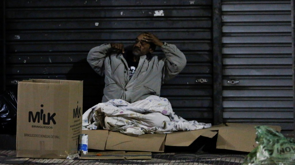 A homeless man gets ready to spend the night on the street in downtown Sao Paulo, Brazil, on June 26, 2016. Earlier this month six homeless people died of cold in Sao Paulo, the richest city in Brazil, where some 16,000 homeless live on the streets. / AFP PHOTO / Miguel Schincariol / TO GO WITH AFP STORY BY ROSA SULLEIRO