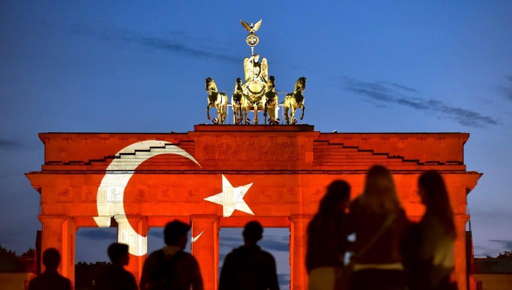 Berlin, 2016. június 30. Emberek nézik a berlini Brandenburgi kaput, amelyre a török zászlót vetítik az isztambuli Atatürk repülõtéren elõzõ napon elkövetett merénylet áldozatai emlékére 2016. június 29-én. A légi kikötõben három merénylõ lövöldözött, majd felrobbantotta magát, amely során legkevesebb negyvenegyen életüket vesztették, kétszázharminckilencen megsebesültek. (MTI/EPA/Klaus-Dietmar Gabbert)