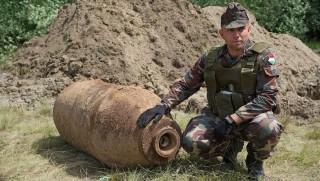 Dabas, 2016. június 16. Ember István őrnagy, vezető tűzszerész az általa hatástalanított, június 7-én a budai Kamaraerdő területén földmunkák közben talált 1000 kilogrammos amerikai GP-2000 légibombával, a felrobbantása előtt, Dabas közelében 2016. június 16-án. Június 13-án a budai Infopark területén is találtak egy kisebb, 500 kilogrammos, amerikai GP-1000 légibombát, azt is ezen a napon semmisítették meg. MTI Fotó: Lakatos Péter