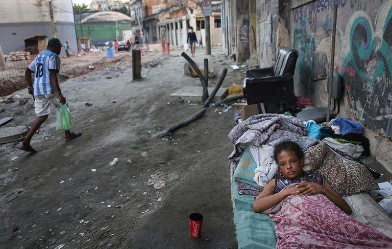 """RIO DE JANEIRO, BRAZIL - JUNE 17: Vanessa, currently homeless, rests on a street where construction of a new VLT (Light Rail System) has been delayed and partially completed in the Port Zone, on June 17, 2016 in Rio de Janeiro, Brazil. While a stretch of the system has partially opened to the public, most other sections are behind schedule to be completed, leaving some streets dilapidated in the midst of delayed construction. The state government of Rio de Janeiro today declared a state of """"public calamity"""" ahead of the Rio 2016 Olympic Games which begin August 5. The statement calls for emergency funding to avoid a collapse in safety, education, health, environmental concerns and transportation. The state and country are in the midst of a severe economic recession. (Photo by Mario Tama/Getty Images)"""