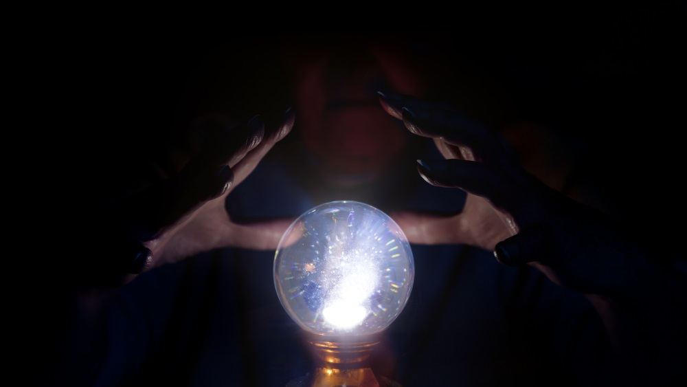 A seer working over a glowing crystal ball, foretelling the future.