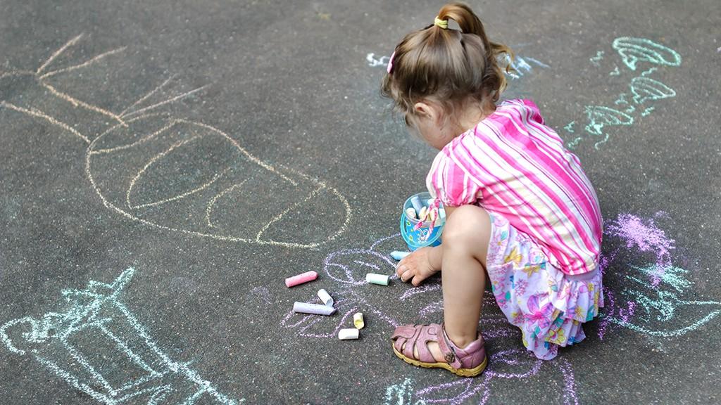 Sidewalk chalk drawings of little Caucasian girl wearing pink ruffle skirt with floral pattern