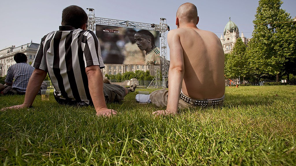 Budapest, 2010. június 11.Két férfi nézi a 2010-es dél-afrikai labdarúgó-világbajnokság Dél-afrikai Köztársaság-Mexikó nyitómérkőzését a budapesti Szabadság téren elhelyezett kivetítő előtt.MTI Fotó: Mohai Balázs