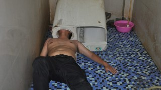A man lies on the ground as his head is stuck in a washing machine in Fuqing county of Fuzhou, Fujian Province, China, May 29, 2016. REUTERS/Stringer ATTENTION EDITORS - THIS IMAGE WAS PROVIDED BY A THIRD PARTY. EDITORIAL USE ONLY. CHINA OUT.