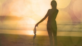 beautiful young lady in great fitness shape standing shy topless at sunset on exotic beach at summer outdoors copy space background with bright sun flares