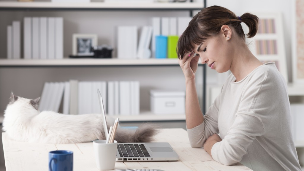 Woman at home, sitting at desk and working with a laptop she is having an headache and touching her forehead, a cat is lying on the desk, illness and stress concept