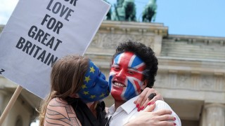 A couple with their faces painted in the flags of the European Union and Great Britain kiss in front of the Brandenburg Gate in Berlin on June 19, 2016.The action, which took place in several cities in Europe, aims to encourage the people in Great Britain to vote in favour of remaining in the EU in next week's referendum.  / AFP PHOTO / dpa / Jörg Carstensen / Germany OUT