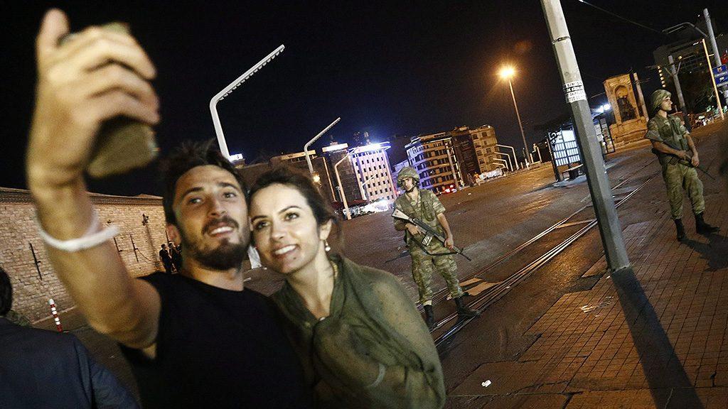 Isztambul, 2016. július 16.Recep Tayyip Erdogan török elnök támogatói fényképezik magukat a katonák által őrzött isztambuli Taksim téren 2016. július 16-án kora hajnalban. A hadsereg egy része katonai puccsot kísérelt meg Törökországban az este, éjfél után azonban még nem volt világos, hogy kinek a kezében van valójában a hatalom. Ankarában és Isztambulban robbanások hallatszottak, és lövöldözés is kitört katonák és rendőrök között. (MTI/EPA/Sedat Suna)