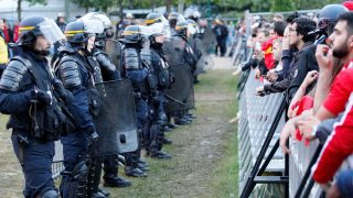 Policemen stand in front of football supporters after firecrackers were heard at the fan zone on the Champ de Mars by the Eiffel Tower in Paris on June 17, 2016 during the Euro 2016 group D football match between Spain and Turkey. / AFP PHOTO / MATTHIEU ALEXANDRE
