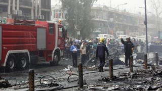 """Iraqis, including firefighters, gather at the site of a suicide car bombing claimed by the Islamic State group on July 3, 2016 in Baghdad's central Karrada district. The blast, which ripped through a street in the Karrada area where many people go to shop ahead of the holiday marking the end of the Muslim fasting month of Ramadan, killed at least 75 people and also wounded more than 130 people, security and medical officials said. The Islamic State group issued a statement claiming the suicide car bombing, saying it was carried out by an Iraqi as part of the group's """"ongoing security operations"""". / AFP PHOTO / SABAH ARAR"""