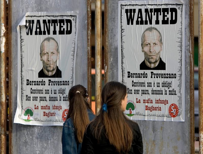 """(FILES) This file photo taken on April 28, 2005 in Bagheria shows women looking at posters bearing pictures of """"Cosa Nostra"""" mafia boss Bernardo Provenzano.     Sicilian """"Cosa Nostra"""" mafia boss Bernardo Provenzano, dubbed """"the tractor"""" for the way he mowed his victims down, has died on July 13, 2016 after a long illness, Italian media said. Provenzano, 83, was the Cosa Nostra crime group's """"boss of bosses"""" until his arrest in 2006 after 40 years on the run, during which he communicated with his lieutenants by word of mouth or typewritten notes. / AFP PHOTO / FABRIZIO VILLA"""