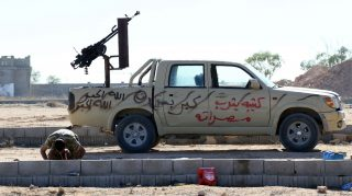 A fighter from the pro-government forces loyal to Libya's Government of National Unity (GNA) prays next to an armed vehicle on July 18, 2016 as they prepare to target Islamic State (IS) group positions in Sirte during an operation to recapture the jihadists' coastal stronghold. / AFP PHOTO / MAHMUD TURKIA
