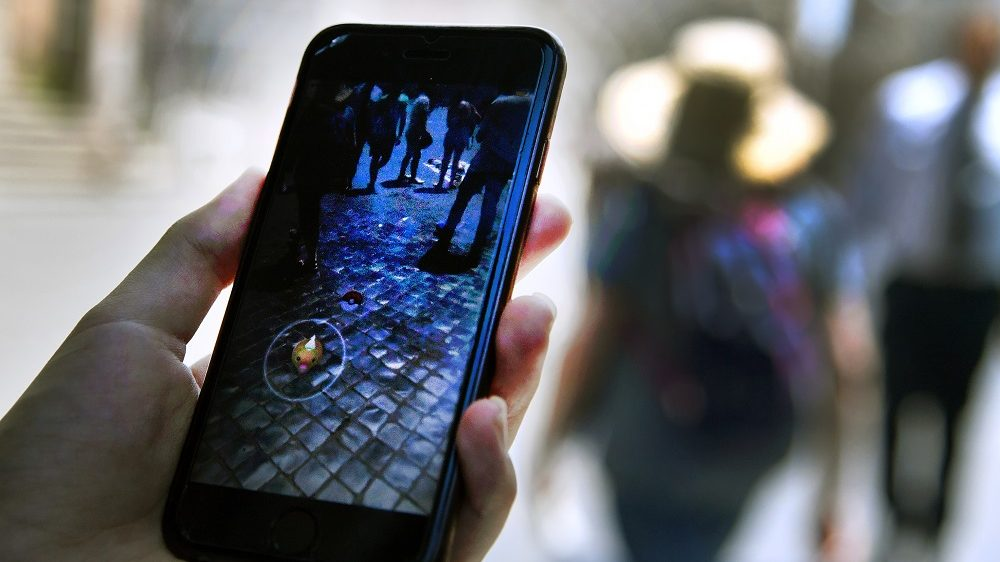 A woman holds her phone as she plays with the Pokemon Go application in central Rome on July 19, 2016. Since its launch two weeks ago, the game for mobile gadgets has sparked a worldwide frenzy among users who have taken to the streets with their smartphones. The free app uses satellite locations, graphics and camera capabilities to overlay cartoon monsters on real-world settings, challenging players to capture and train the creatures for battles.  / AFP PHOTO / TIZIANA FABI