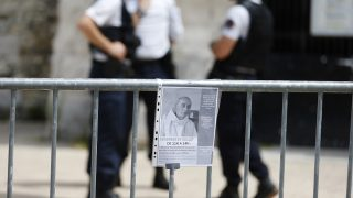 """A picture taken on July 28, 2016 shows a fence with a note including a picture of French priest Jacques Hamel, killed on July 26 in the church during a hostage-taking claimed by Islamic State group,   and a call for a mass in his memory on July 29, near French police forces in front of the church of Saint-Etienne-du-Rouvray, northern France. French prosecutors on July 28, 2016 identified the second jihadist involved in the brutal killing of an elderly priest, as calls mounted for the prime minister and interior minister to resign after the latest terror attack. The prosecutor's office named the assailant as 19-year-old Abdel Malik Petitjean, who was listed in June on France's """"Fiche S"""" of people posing a potential threat to national security after trying to reach Syria from Turkey.  / AFP PHOTO / CHARLY TRIBALLEAU"""