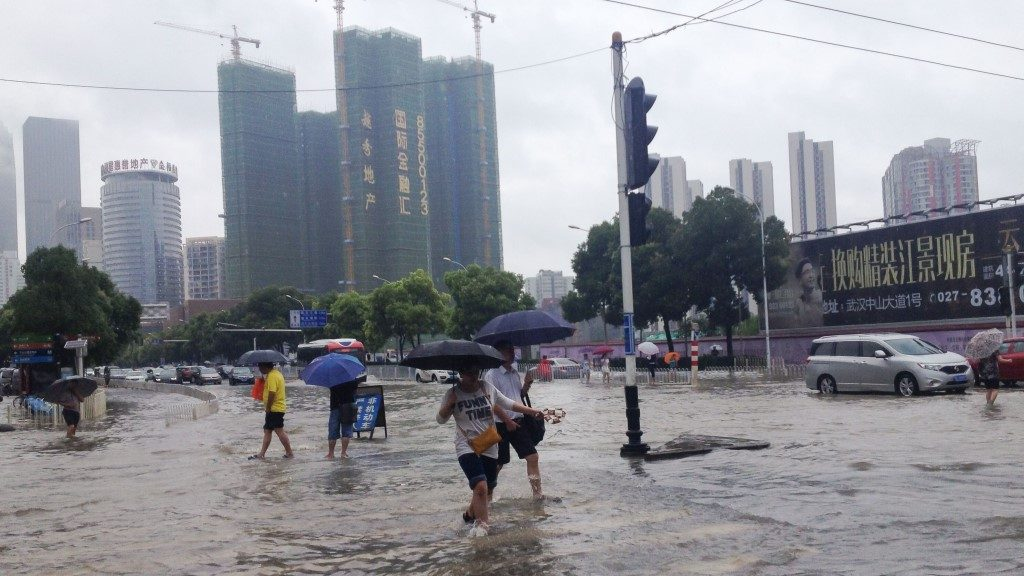WUHAN, CHINA - JULY 6 : People walk in flood water after a heavy rainfall caused flood in Wuhan, China on July 6, 2016.Transport links and water and power supplies in Wuhan are severely affected, and some are trapped in their homes. Stringer / Anadolu Agency