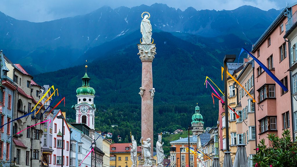 A view along Maria-Theresien-Strasse in Innsbruck during the day. The Annasaule column and the outside of buildings can be seen and mountains can be seen in the distance.
