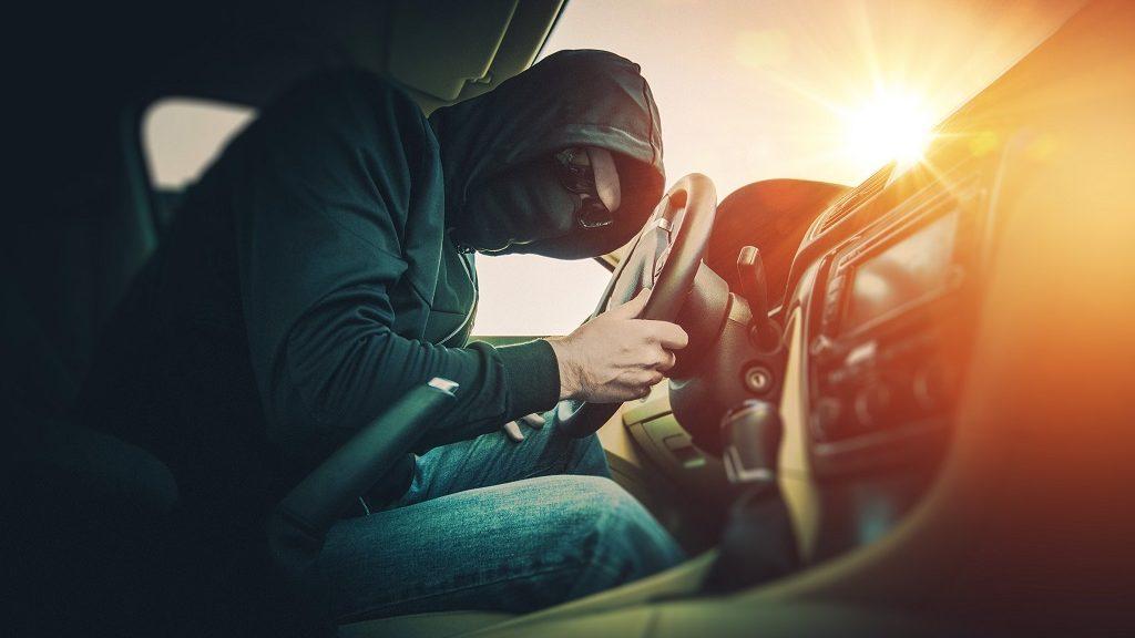 Car Thief in a Black Mask and Black Glasses. Car Thief Inside the Modern Car.