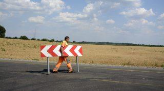 Jászfényszaru, 2015. július 1. Egy munkás elviszi a terelõtáblát az új közúti híd felé vezetõ autóúton, Jászfényszaru határában 2015. július 1-jén. A Szolnok-Hatvan vasútvonal feletti új közúti híd a 32-es út felújítása részeként épült meg. MTI Fotó: Mészáros János