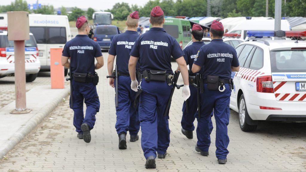 """Röszke, 2015. június 25. A Készenléti Rendõrség munkatársai a röszkei hangárnál 2015. június 25-én. Az épületben és a szomszédságában felállított sátrakban õrzik az elsõ 24 órában azokat a határsértõket, akiket Csongrád megyében fogtak el. A rendõrség bevetési osztályának több tagja jelent meg a helyszínen, miután a hangárból """"Freedom!"""" (Szabadság!) és """"UN!"""" (ENSZ!) felkiáltások hallatszottak. A rendõrség szerint kisebb konfliktus történt, nem kellett beavatkozniuk. MTI Fotó: Kelemen Zoltán Gergely"""