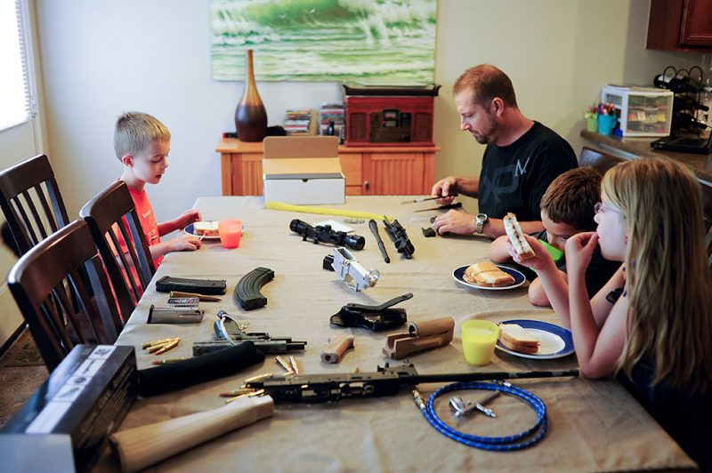 SAN ANTONIO, TEXAS - August 8, 2012: Thomas cleaning his guns at the table while his children have breakfast. (Photo by Eric O'Connell/ASAblanca via Getty Images)