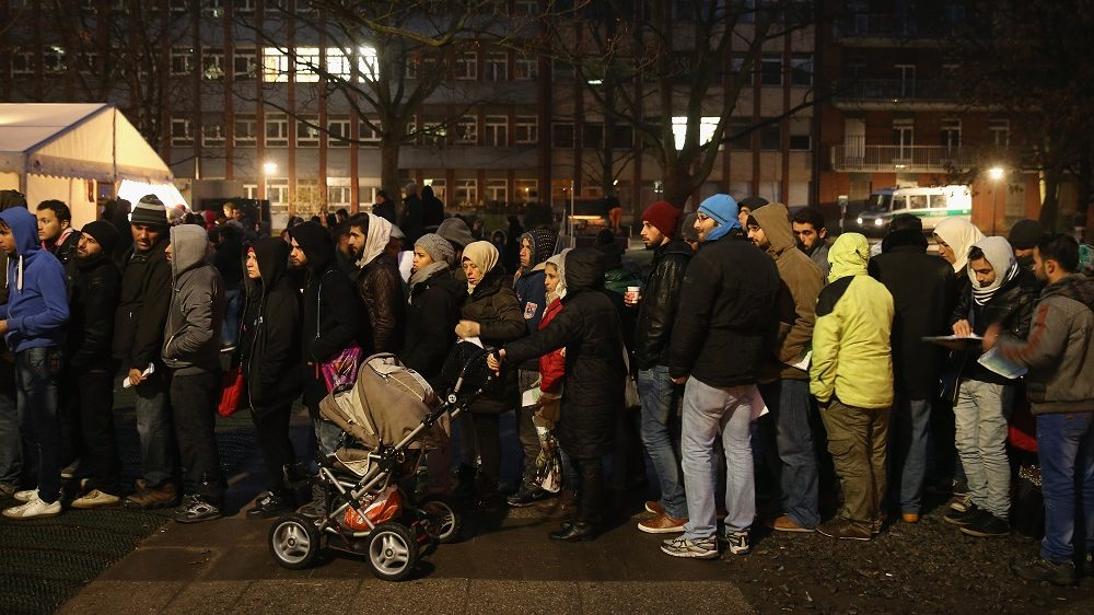 BERLIN, GERMANY - DECEMBER 09:  Migrants and refugees wait in the early hours outside the Central Registration Office for Asylum Seekers (Zentrale Aufnahmestelle fuer Asylbewerber, or ZAA) of the State Office for Health and Social Services (Landesamt fuer Gesundheit und Soziales, or LAGeSo) on December 9, 2015 in Berlin, Germany. Migrants receive benefits, including housing vouchers and cash, at LAGeSo, and the office is currently so overwhelmed with the volume of applicants that migrants are waiting days on end to be admitted to the building. The German Minister of the Interior recently announced that 965,000 people applied for asylum between January and November of this year, putting the country well on track to pass the one million mark by the end of the year.  (Photo by Sean Gallup/Getty Images)